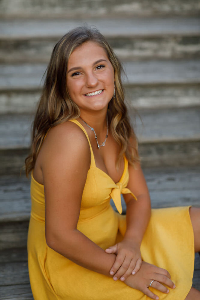 Senior girl in yellow dress on steps at Forest Park Springfield